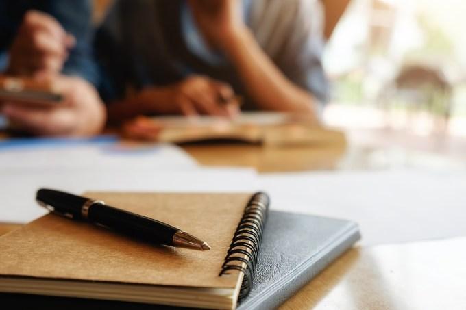 Estudantes, cadernos, caneta e papéis
