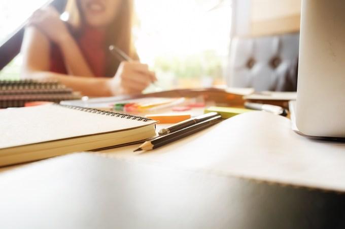 Estudante escrevendo em um caderno