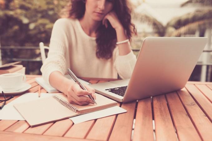 Estudante escrevendo e estudando no computador