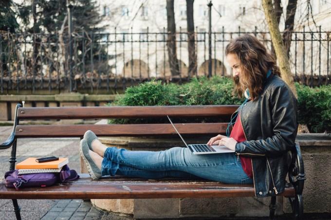 Estudante digitando em um laptop e estudando no banco de um jardim