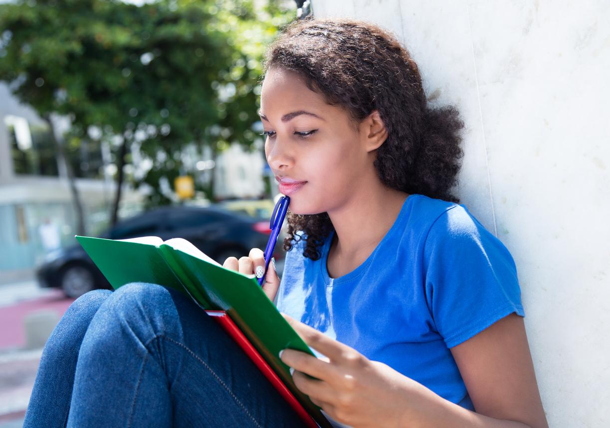 Estudante preenchendo caderno