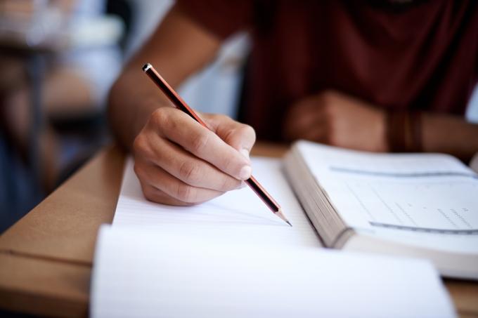 Estudante escrevendo em caderno
