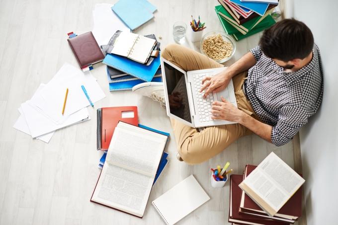 Jovem estudando em um laptop, com materiais escolares, como livros e cadernos,