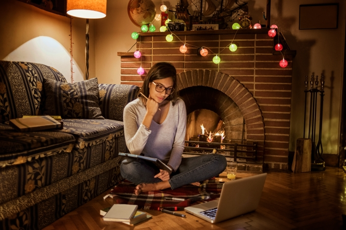 Jovem estudando em um laptop, com luzinhas e livros espalhados