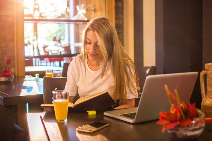 Garota estudando em um café, com um laptop e um livro, enquanto toma um suco