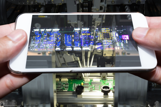 Hand holding smartphone scanning printed circuit board by application, Industry 4.0 concept