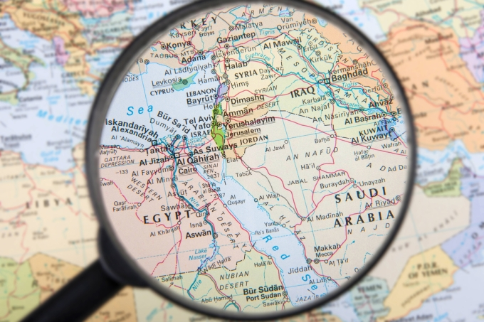 A magnifier zooming in Middle East countries on a global map