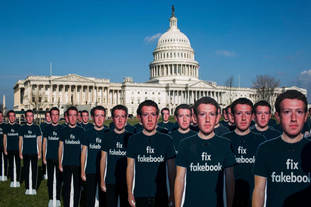 Cartazes em protesto contra Mark Zuckerberg, em frente ao Congresso norte-americano, em abril de 2018. A inscrição na camiseta diz