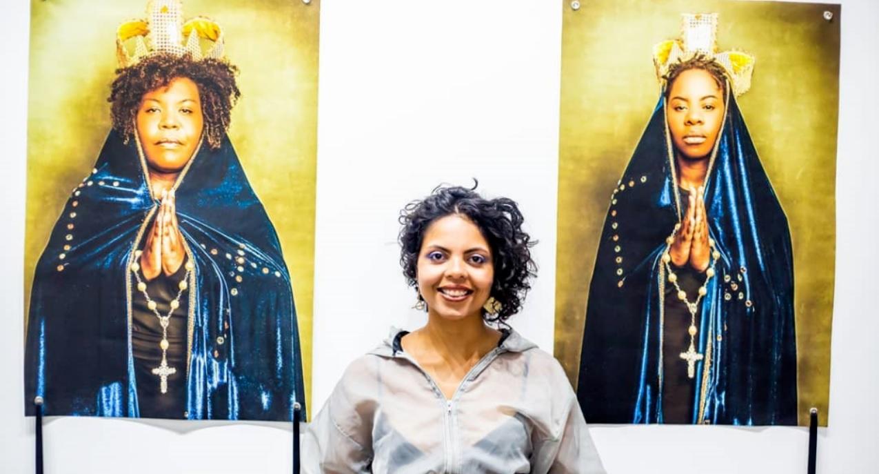 Linoca Souza ao lado de duas imagens de mulheres negras vestidas como figuras religiosas católicas
