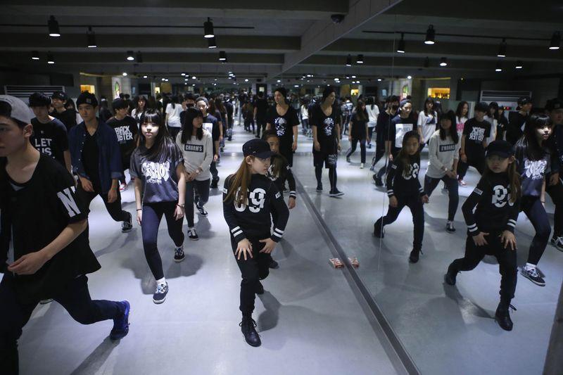 Grupo de jovens treinando para a indústria do K-Pop.
