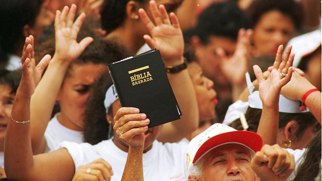 Homem segura uma bíblia em culto de uma igreja evangélica neopentecostal
