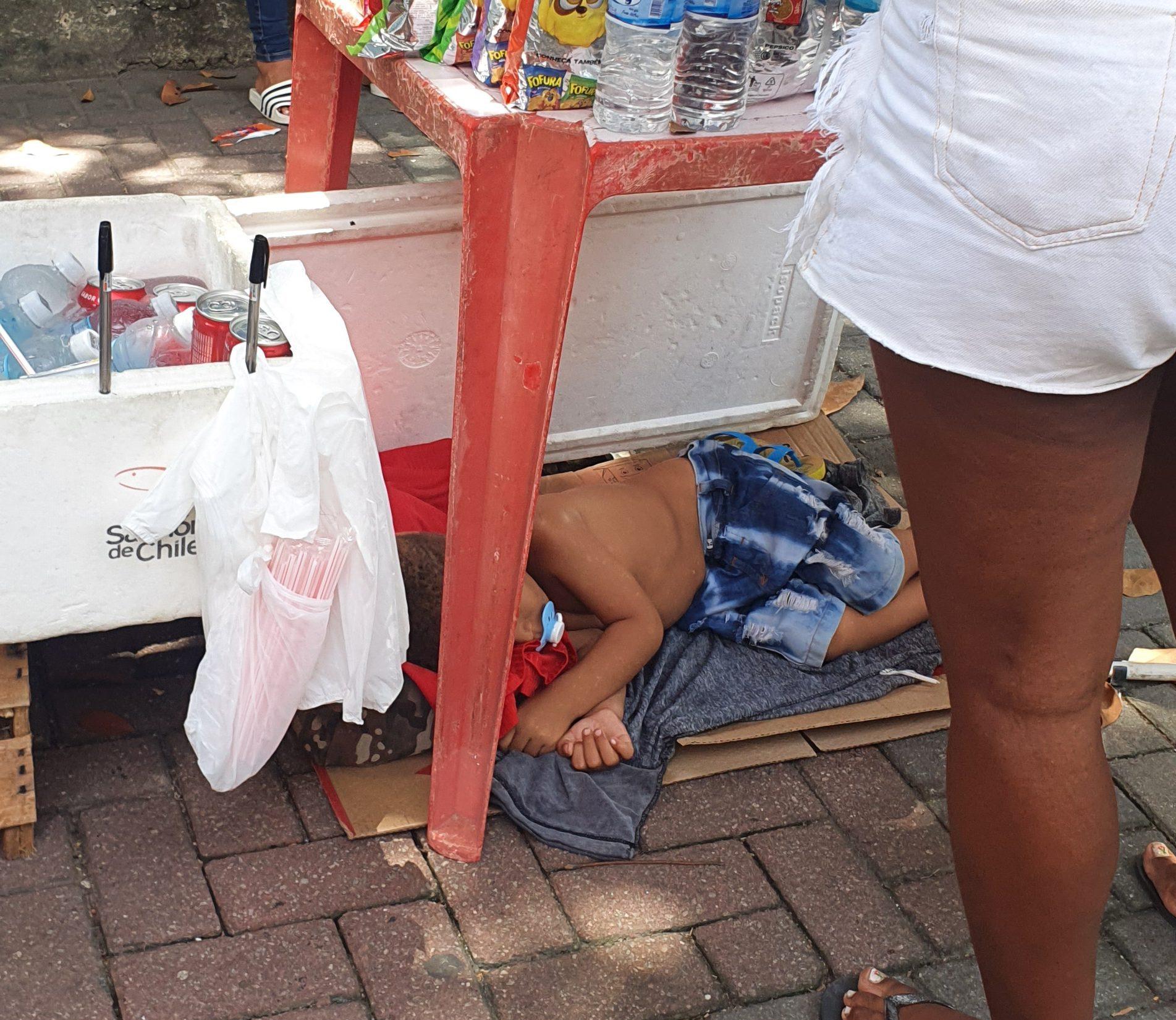 Criança dorme sob banca de ambulante na entrada do Enem