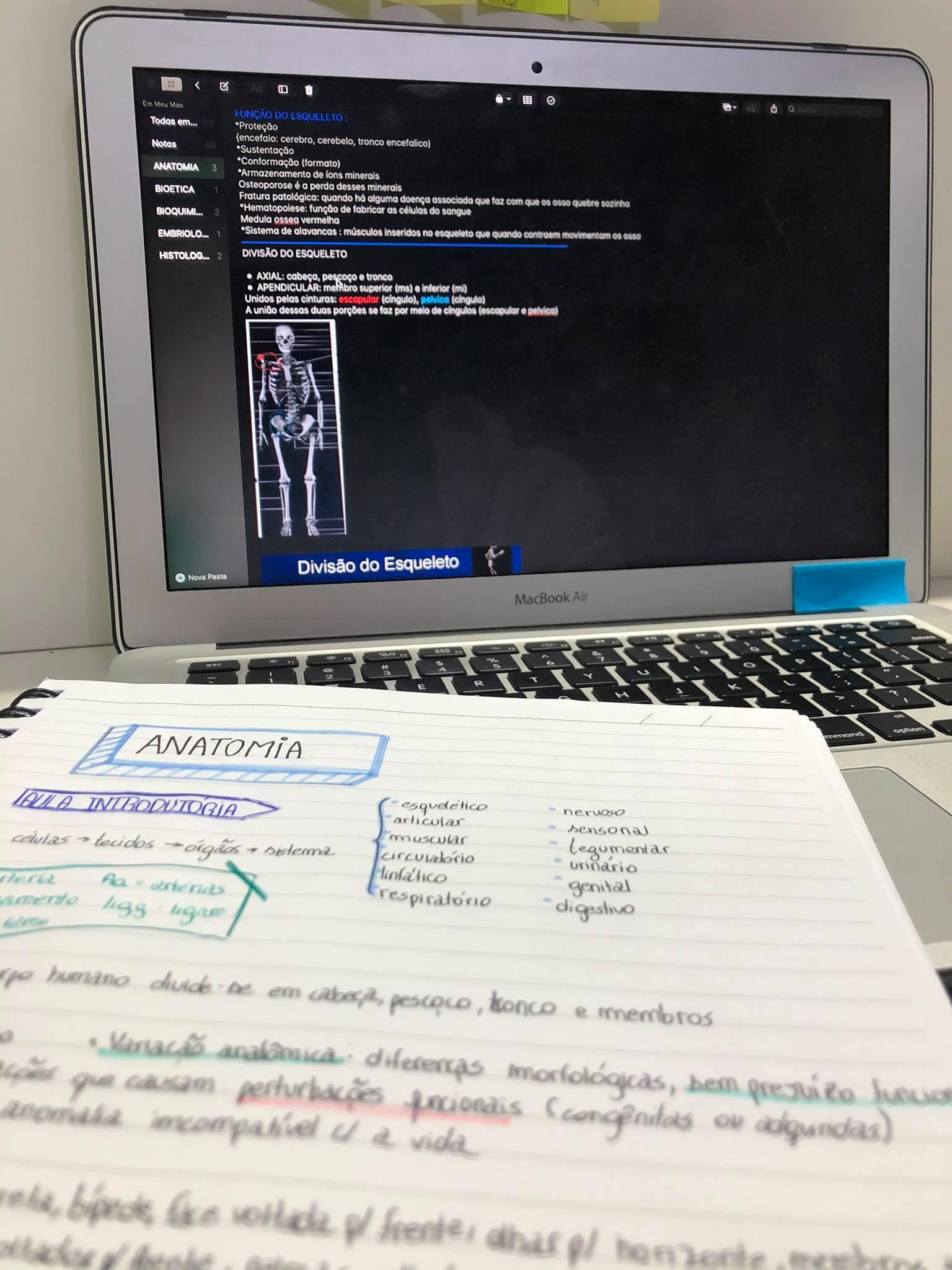 Um caderno com anotações de Anatomia, em frente ao computador, que mostra parte da aula