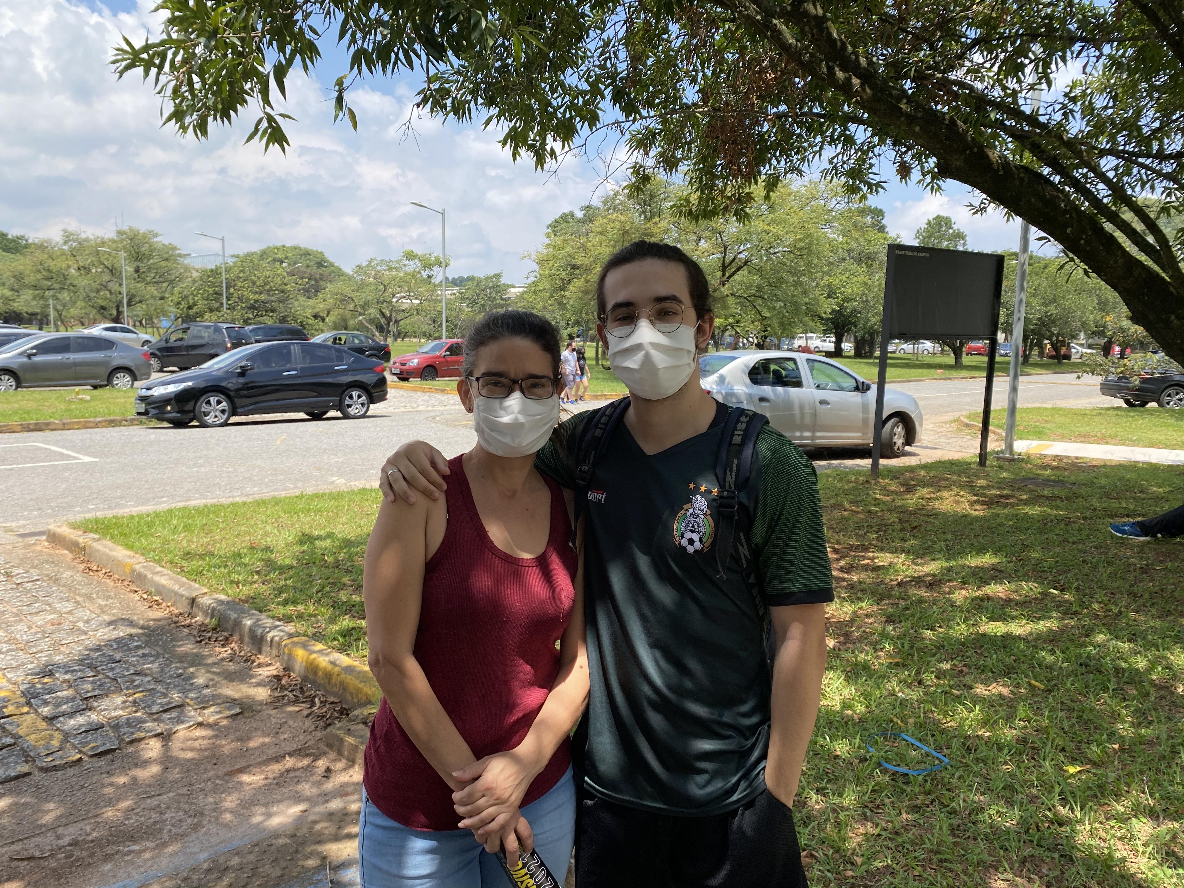 Mãe e filho se abraçam na sombra, ambos de máscara.