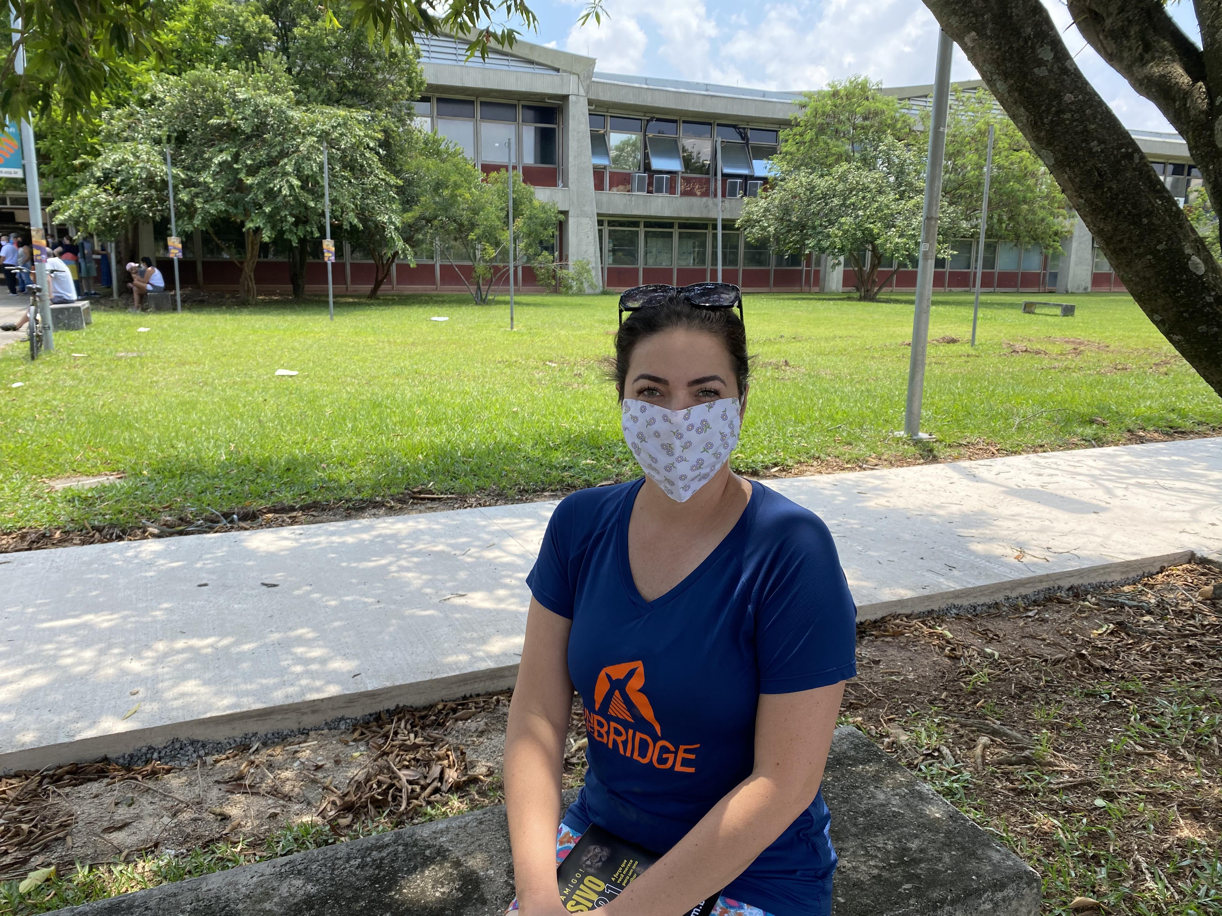 Daniela está sentada em um banco ao lado da entrada do local de prova. De máscara, ela se abriga do sol debaixo de uma árvore.