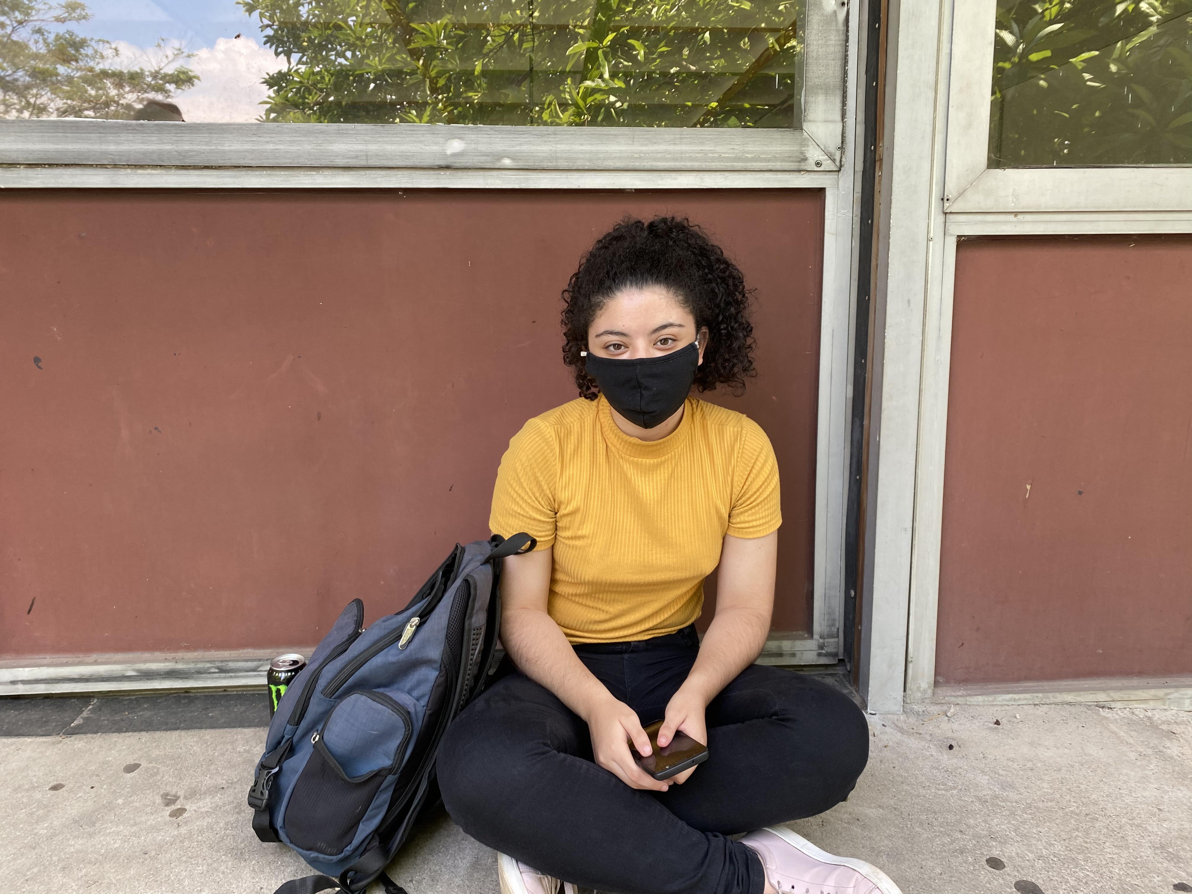 Estudante sentada no chão e de máscara.