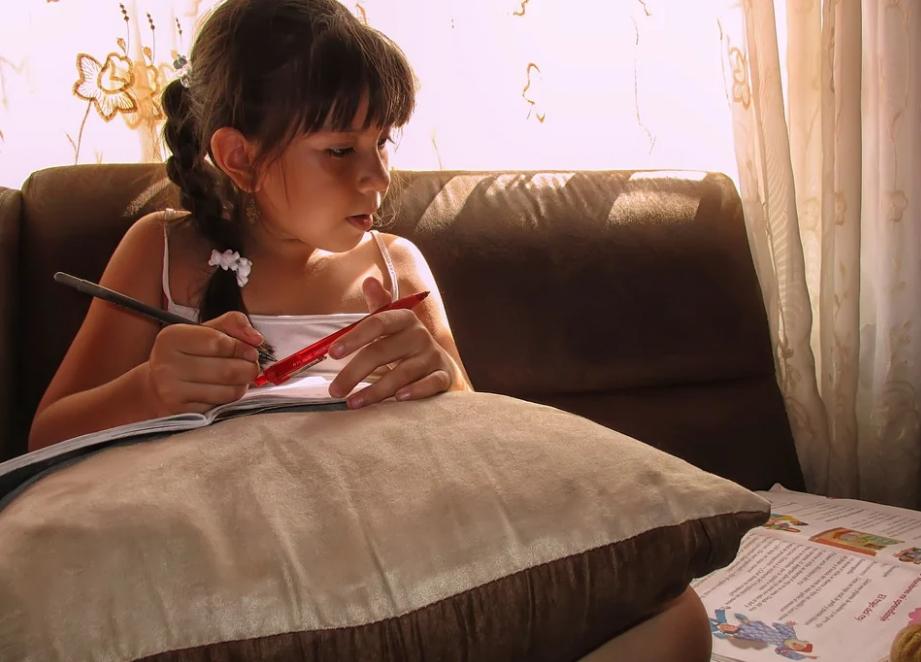 Menina estudando em casa com livro didático