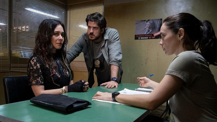 Numa sala de interrogatório, Eric (Marco Pigossi) fala com uma investigadora e com Inês, personagem que representa a Cuca.
