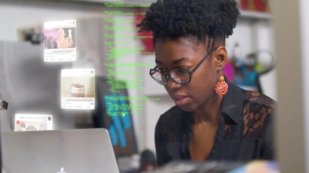 Pesquisadora do MIT Joy Buolamwini em frente de um notebbok