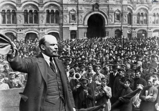 O líder Lenin, do partido bolchevique, acena para a população durante uma passeata. Nas ruas, uma multidão se aglomera para ver o político.