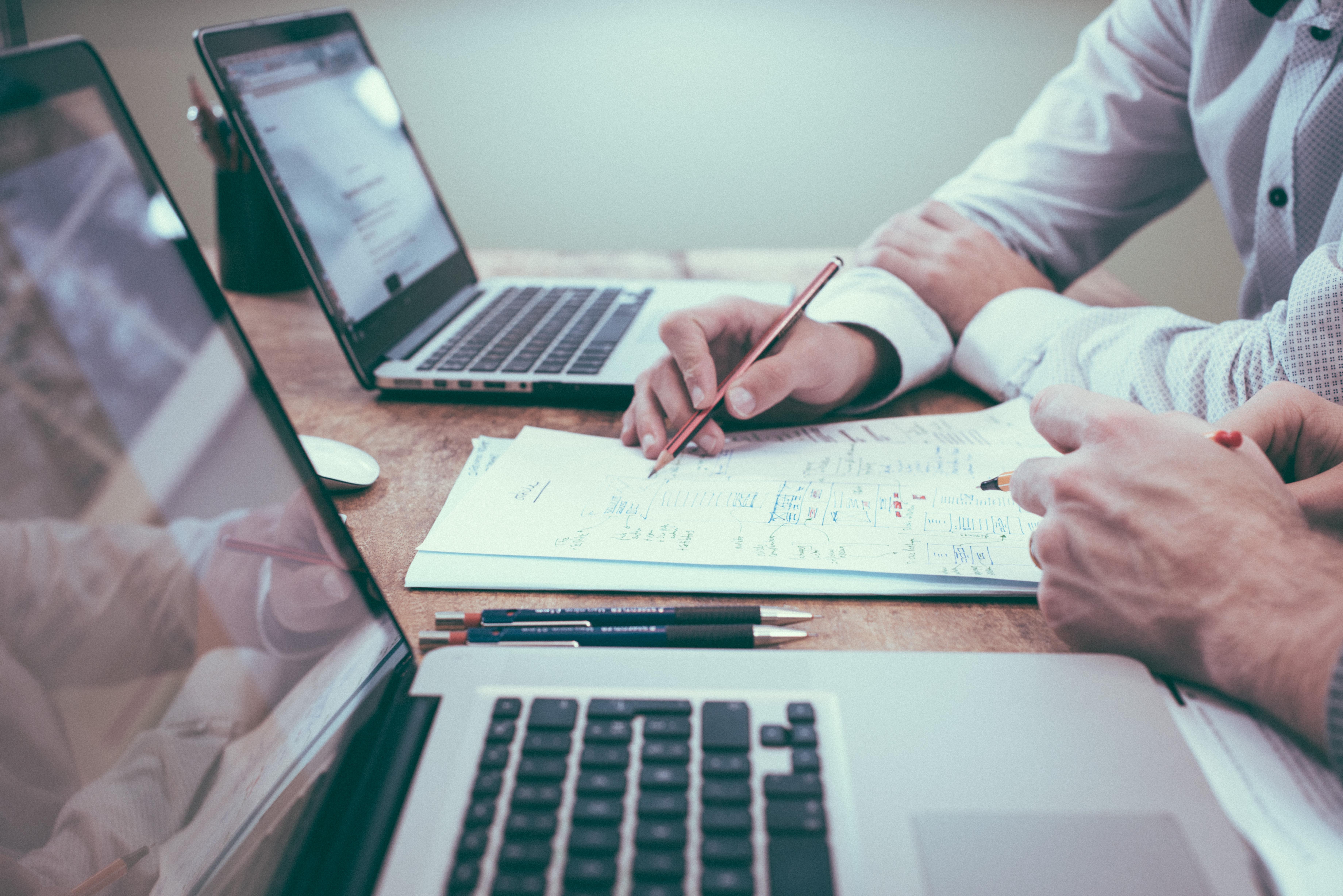 Mesa de trabalho, com dois computadores, folhas de anotação e duas pessoas fazendo contas.