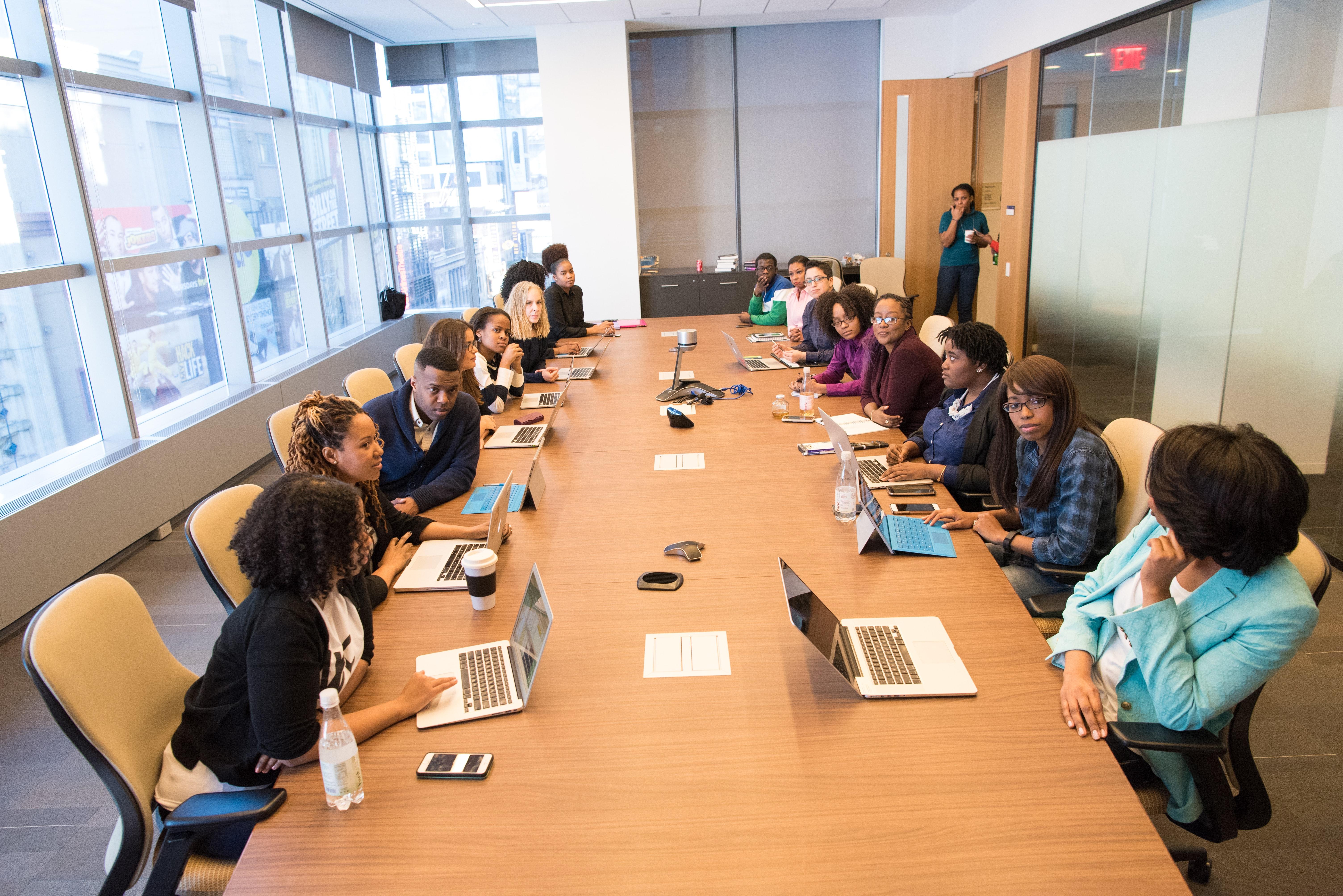 Mesa de trabalho, em que cerca de vinte pessoas conversam com folhas e lápis em suas mãos