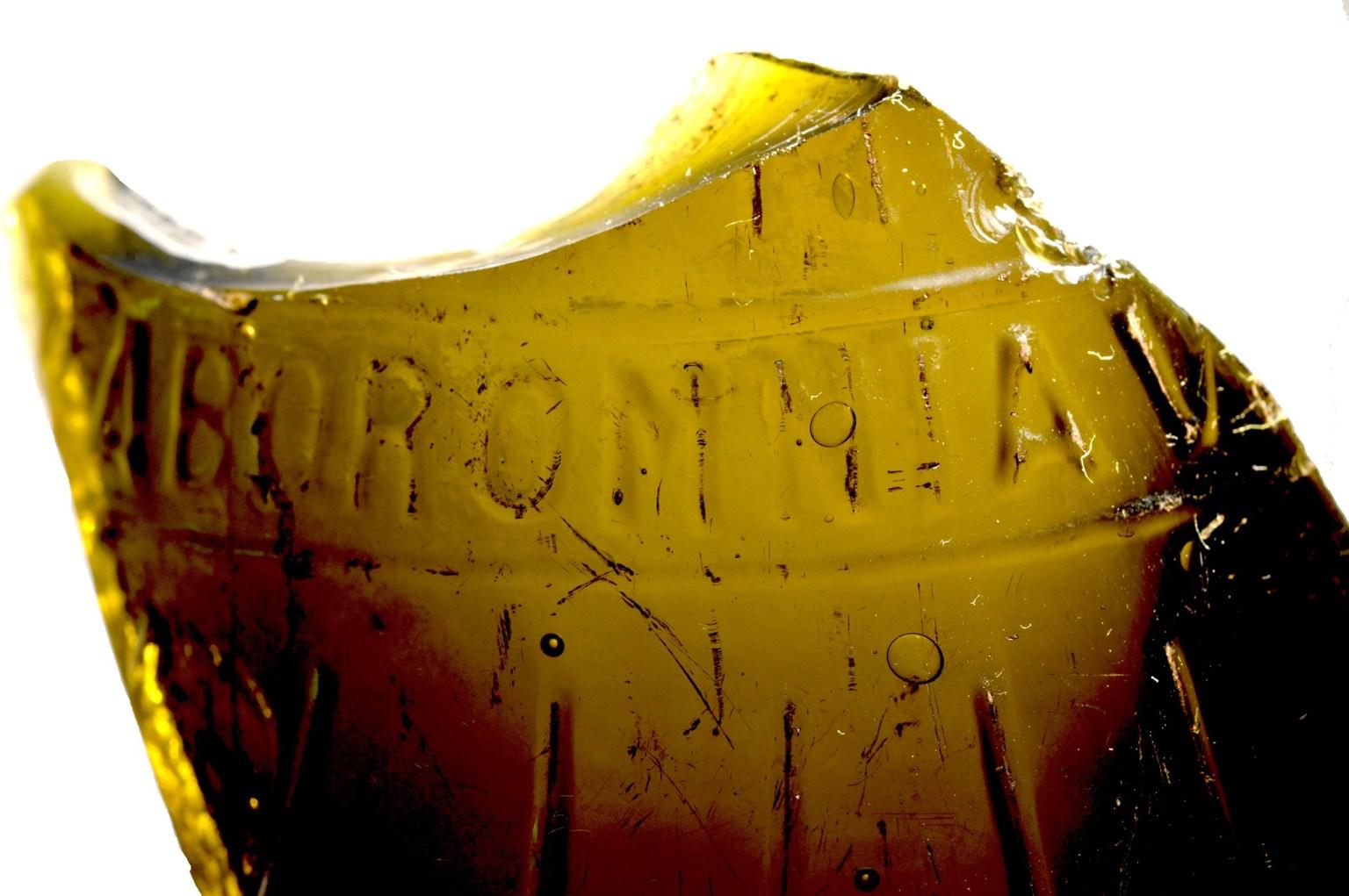 """Fragmentos de vidro, provavelmente do período entre o final do século 19 e o início do século 20. Provavelmente de uma garrafa de vidro com a inscrição """"Labor omnia V"""