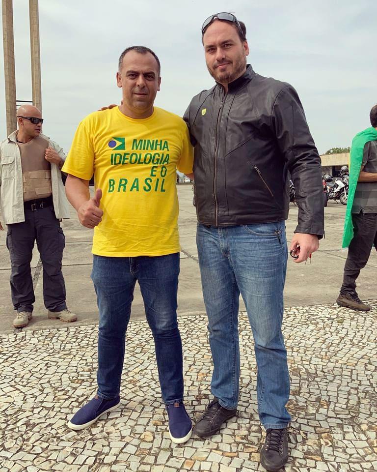 O deputado Anderson Moraes posa ao lado do vereador Carlos Bolsonaro (Republicanos) no dia 23 de maio de 2021. Ambos estão sem máscara. Moraes usa uma camisa amarela escrito em verde