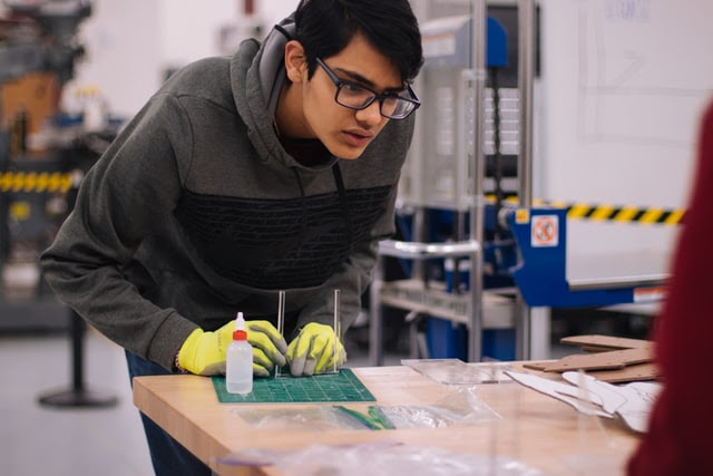 Estudante apoiado em uma mesa, de óculos e luva