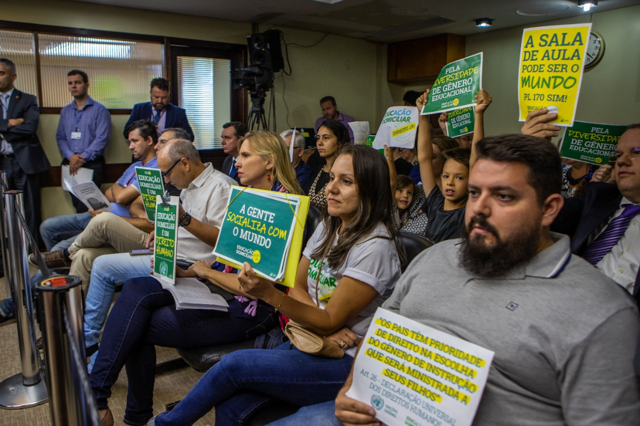 Homens, mulheres e crianças, de diferentes idades, acompanham sentados audiência. Estão segurando cartazes com dizeres que defendem o ensino domiciliar.