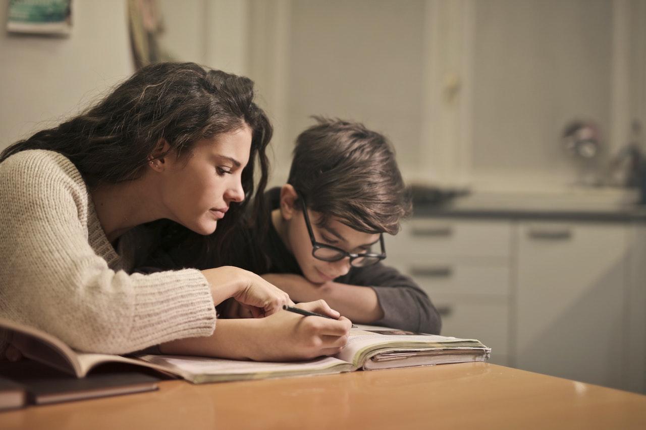 Mulher se apoia ao lado de um menino, que está lendo um livro. Os dois estão sentados em uma mesa dentro de um ambiente fechado.