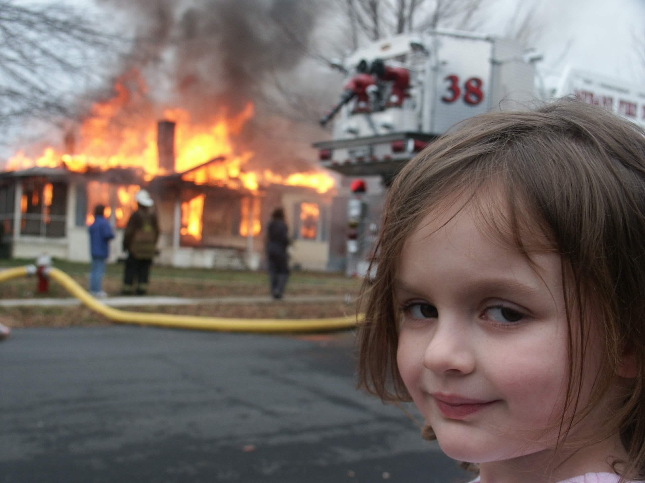 Menina olha diretamente para a câmera com olhar maléfico enquanto uma casa em chamas é socorrida pelos bombeiros.
