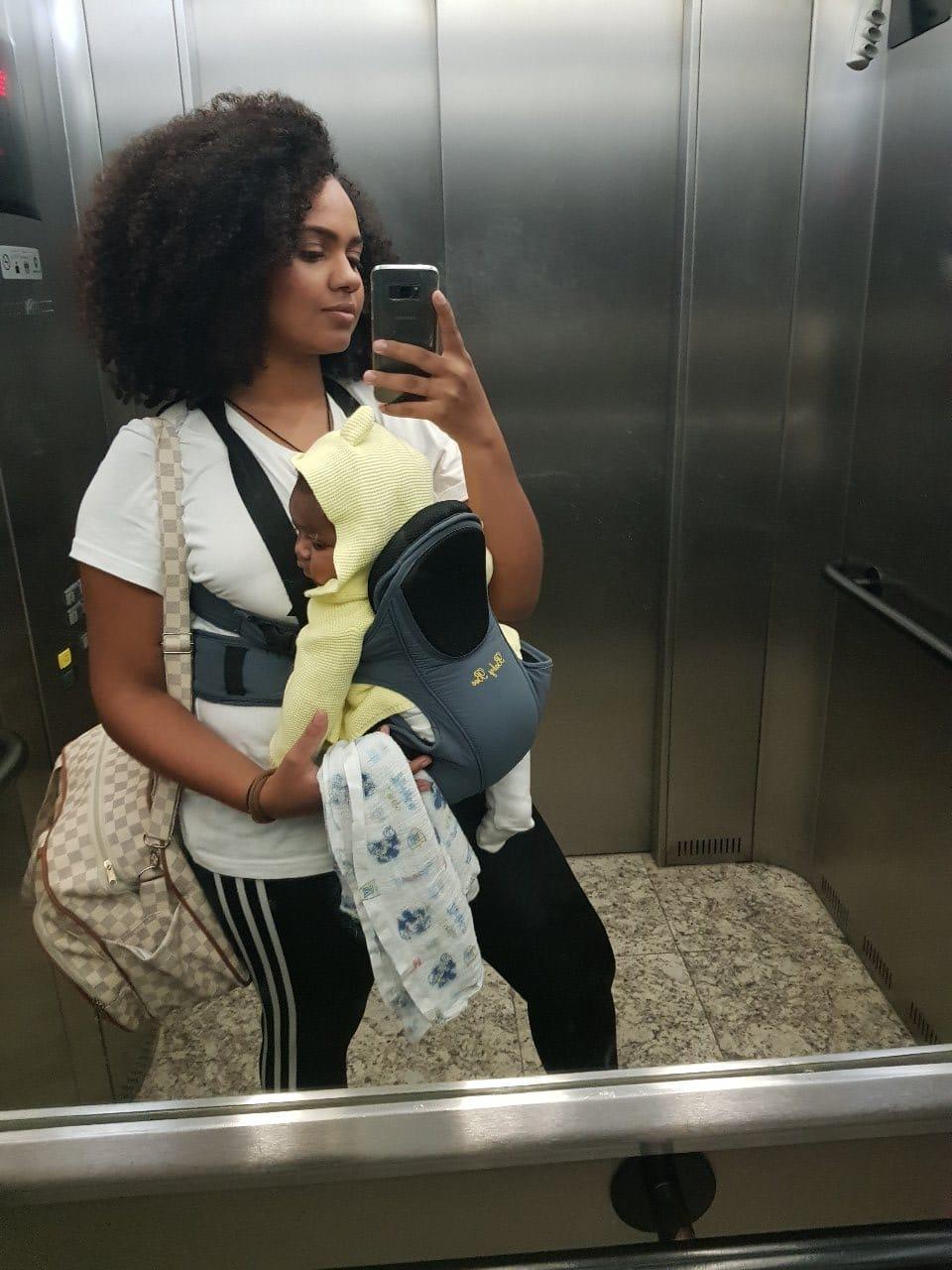 Mãe com filho em um canguru para bebê dentro do elevador