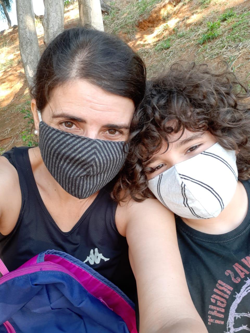 Mãe e filho de máscara no parque