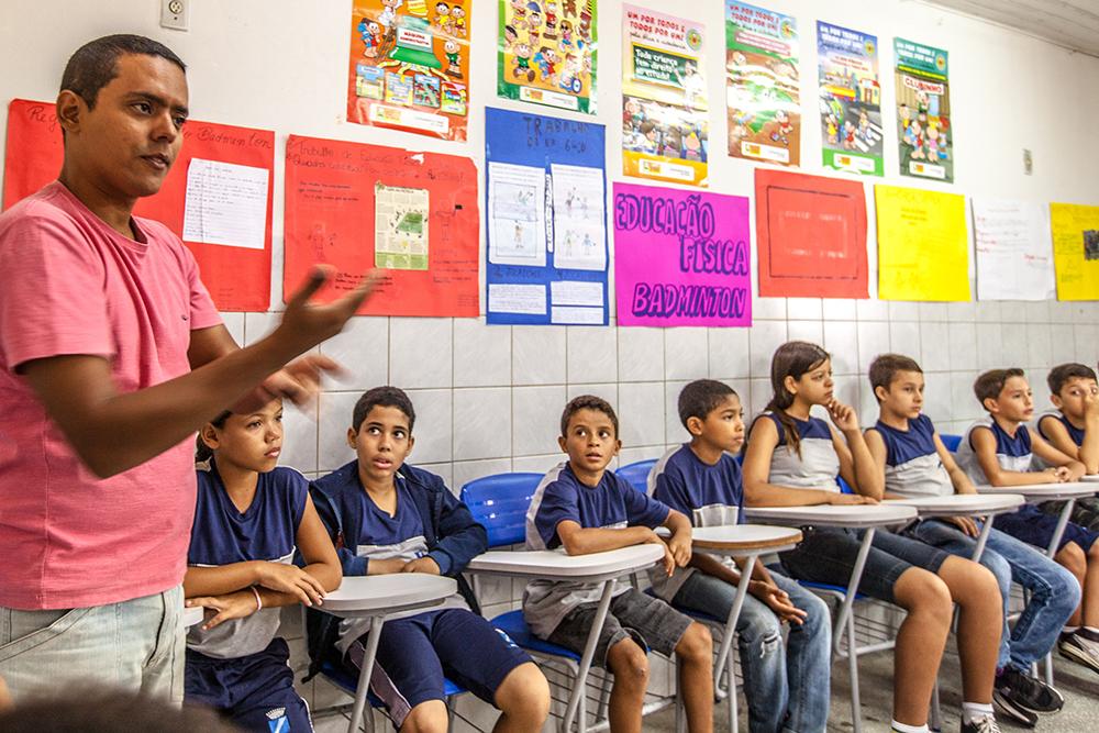 Professor em pé aparece falando com alunos, sentados em carteiras. Estão dentro de uma sala d aula, com diferentes cartazes coloridos estampando as paredes.
