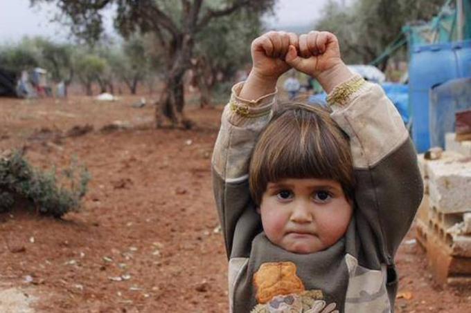 Adi Hudea, uma menina síria, ergue os braços e fecha as mãos em gesto de rendição, após confundir a câmera fotográfica com uma arma
