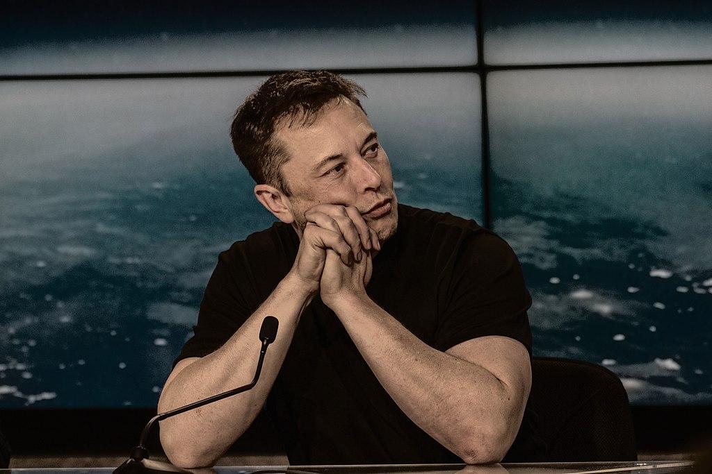 Homem de camiseta preta, com as mãos apoiados no queixo, olha para o lado. Ele parece estar sentado em uma bancada, e há um microfone em sua frente.