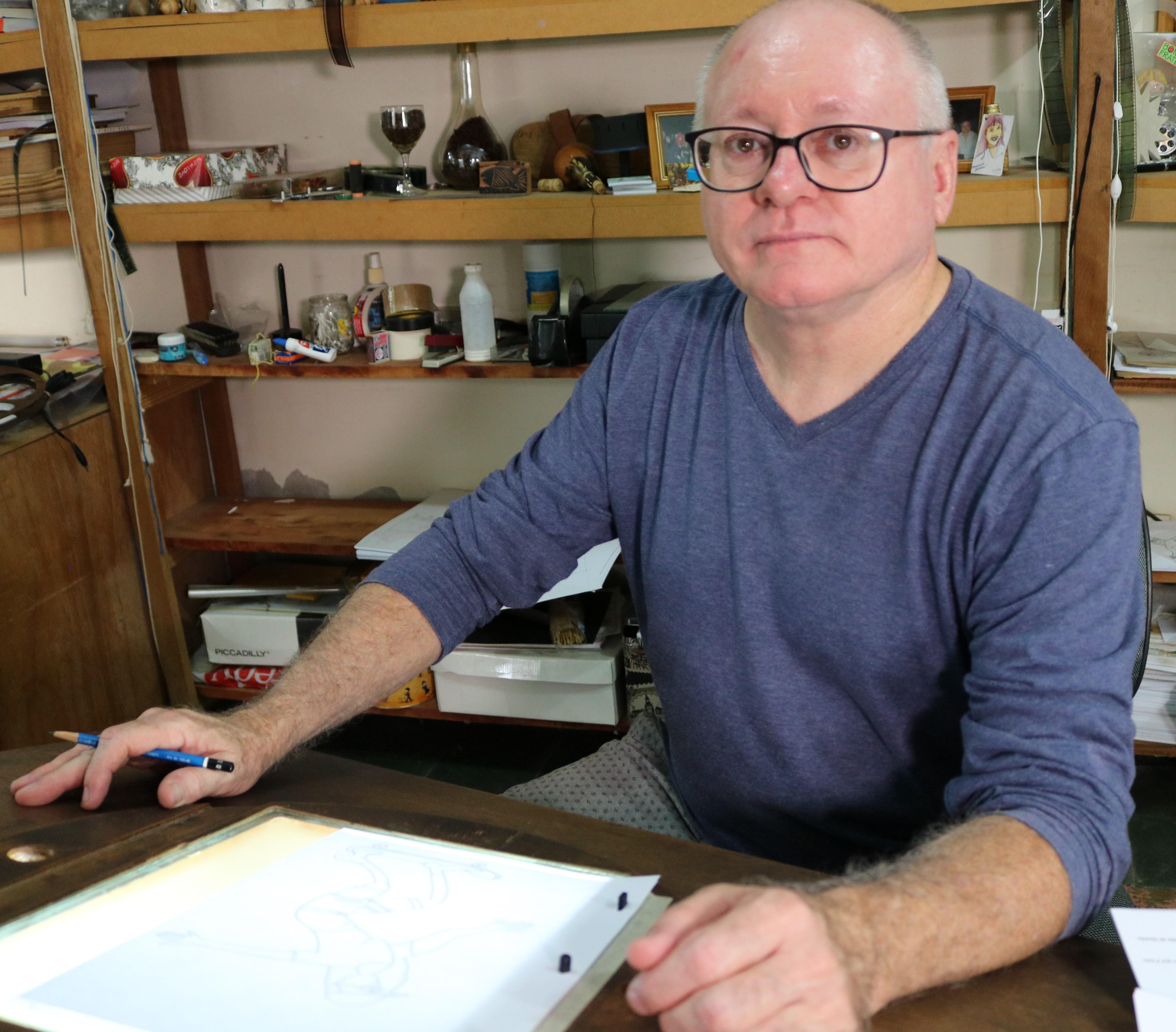 Homem branco adulto, usando óculos e camiseta azul, é careca e com cabelos brancos na lateral da cabeça. Está sentado em uma mesa com um caderno aberto em sua frente enquanto segura um lápis. Ele olha diretamente para a câmera.