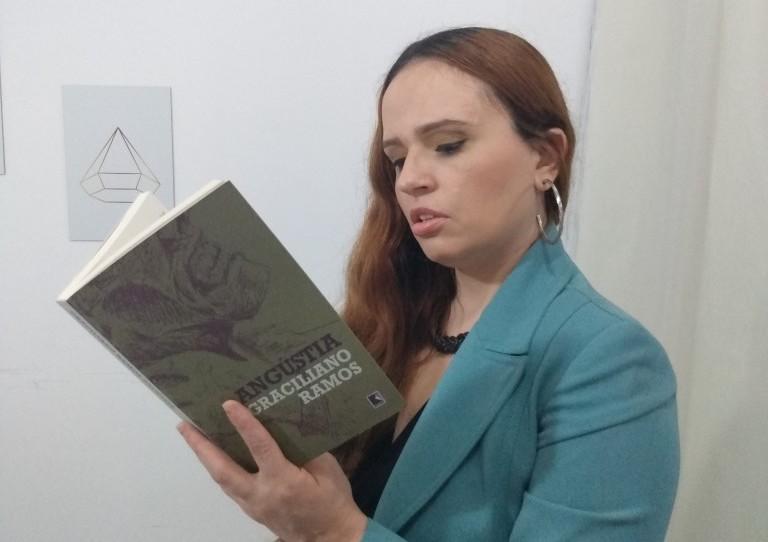 Mulher branca, de cabelos cobreados, usando um blazer turquesa, em pé, lendo o livro aberto 'Angústia', de Graciliano Ramos.