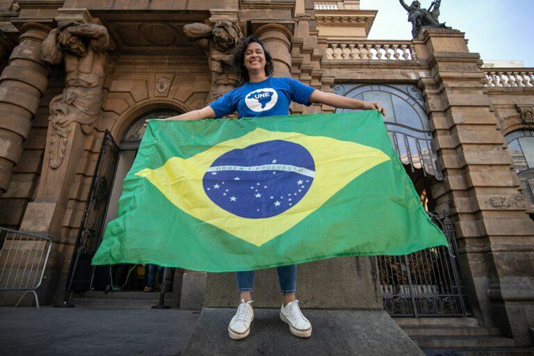 Jovem negra de cabelos castanhos na altura dos ombros veste camiseta azul com o símbolo da UNE enquanto estende a bandeira do Brasil com os dois braços. Ela está em frente ao Teatro Municipal, em São Paulo,