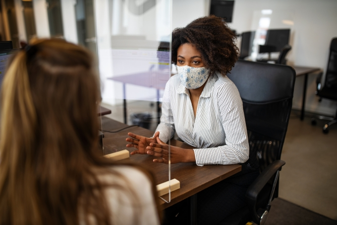 Mulheres conversam em um escritório. Elas usam máscaras e há um protetor de espirro entre elas.