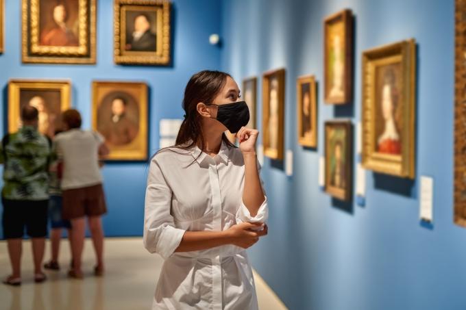 Jovem visita um museu de arte e usa máscara de proteção
