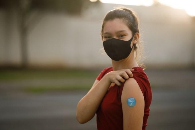 Teenage girl showing her covid 19 vaccine badge